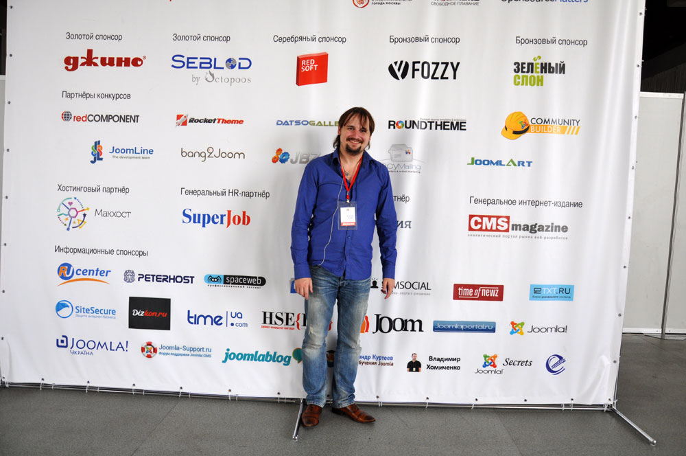 Dmitry stands on a background of JoomlaDay Russia 2014 sponsors. Here we are too :-)